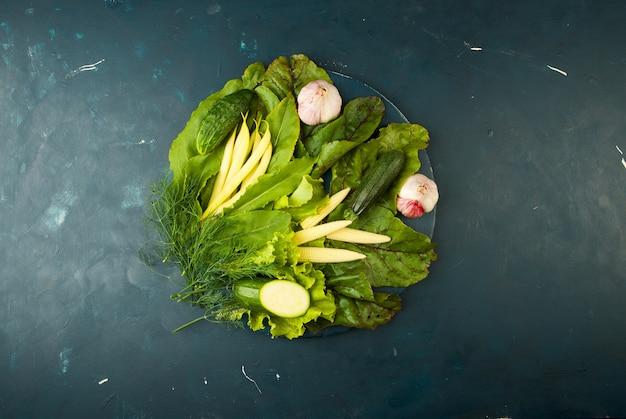 Les legumes dans la boite sur la pierre un fonce. les épices lumineuses de zucchini à l'ail et aux jeans vert d'oignons sont dans une boîte en bois avec des poignées de corde sur un texturé foncé.