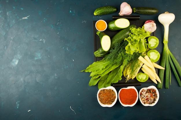 Les legumes dans la boite sur la pierre un fonce. les épices lumineuses de zucchini à l'ail et à l'œil vert jouent dans un plateau en bois avec des poignées sur un texturé foncé.