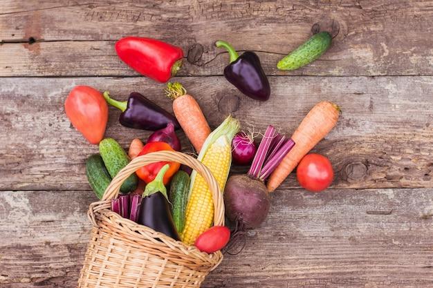 Légumes dans un panier en osier sur un fond en bois. des cultures fraîches, des produits de la ferme, un potager à la maison. espace de copie