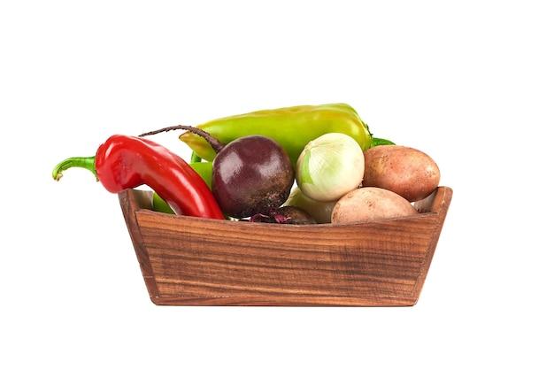 Légumes dans un plateau en bois sur blanc.