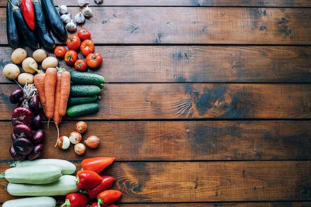 Légumes de différentes couleurs sur un fond texturé foncé avec une place vide pour une vue de dessus d'inscription.