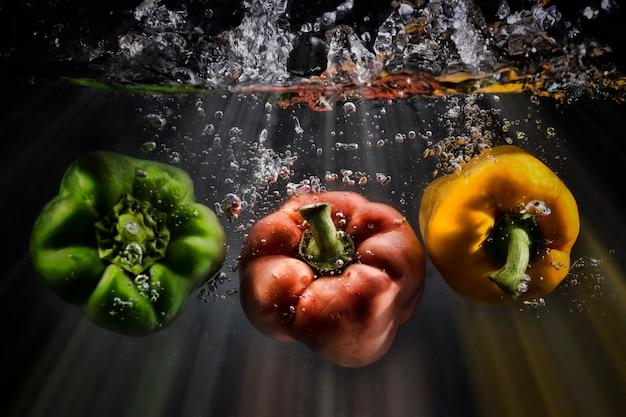 Légumes éclaboussent l'eau sur fond noir