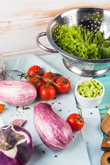 Des légumes; épices et passoire sur la nappe au-dessus de la table en bois