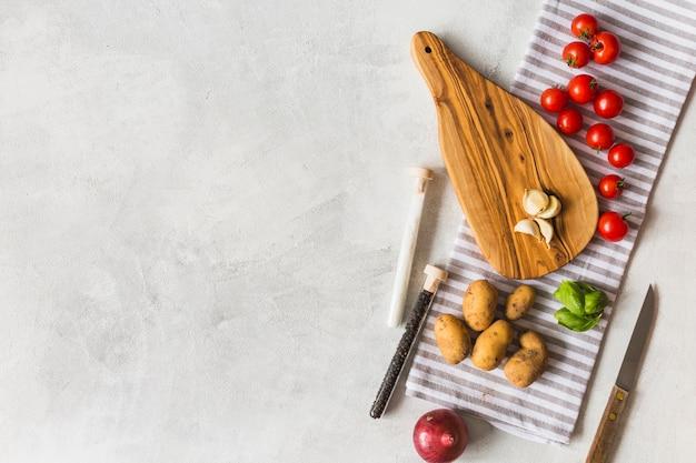 Des légumes; éprouvettes de sel et de poivre noir et planche à découper sur une serviette sur fond blanc