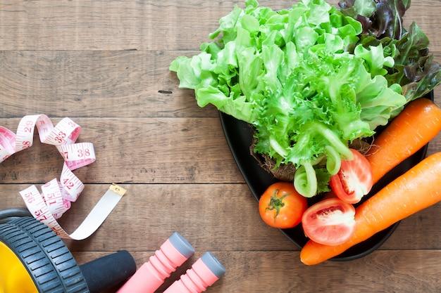 Légumes et équipements de fitness sur fond en bois