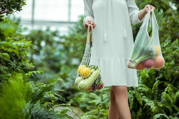 Des légumes. femme en robe blanche portant des sacs avec des légumes
