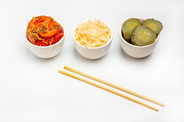 Légumes fermentés, choucroute, cornichons de conservation salés concombre et tomates sur fond blanc. alimentation équilibrée. cuisine végétarienne biologique