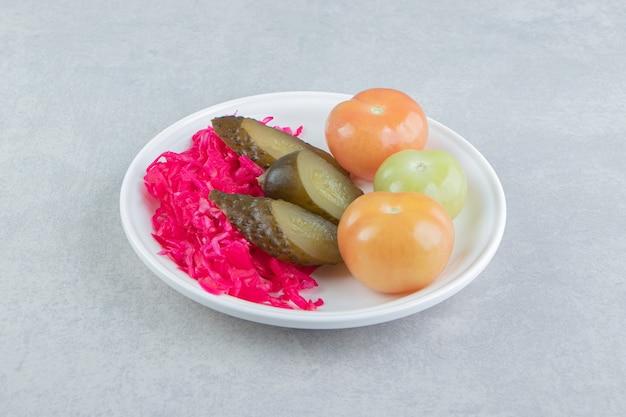 Légumes fermentés et choucroute sur plaque blanche.