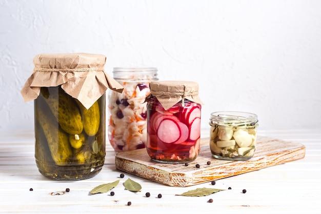 Légumes fermentés, marinés, chou, concombres, radis et ail dans un bocal en verre sur fond clair avec espace copie. orientation horizontale