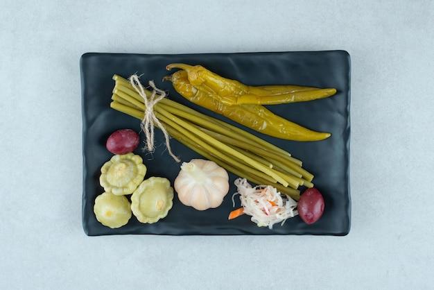 Légumes fermentés mixtes sur plaque noire.