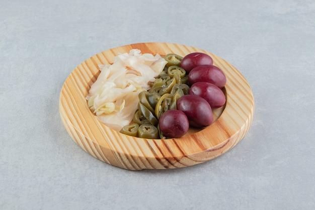 Légumes fermentés placés sur plaque de bois.