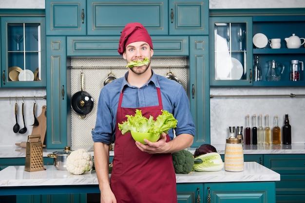 Les légumes à feuilles sont un bon choix pour une alimentation saine. préparez la salade parfaite. la salade verte contient de nombreux nutriments. chef cuisinier salade verte. ajouter à votre alimentation. bienfaits de la salade pour la santé. homme affamé dans la cuisine.