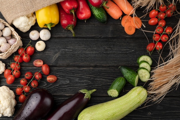 Légumes sur fond de bois sombre, nature morte de légumes joliment décorée.