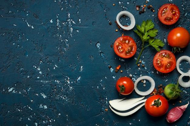 Légumes frais (ail, tomates, oignons) sur une surface sombre en relief.