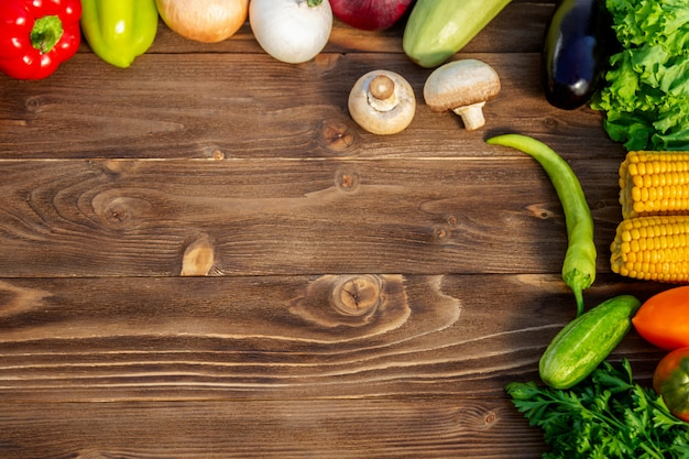 Légumes frais, aubergines, courgettes, poivrons, oignons, laitue, persil, tomates, maïs pour une alimentation saine et une alimentation sur bois brun