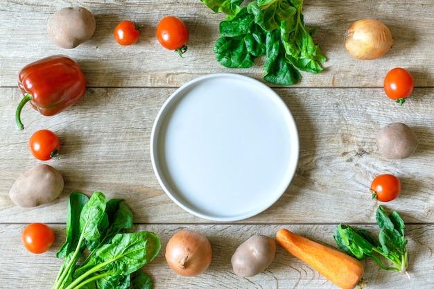 Légumes frais biologiques et bio avec plaque en céramique vide au fond de table rustique en bois. concept de légumes végétariens mûrs naturels sains