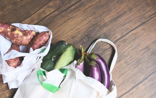 Légumes frais biologiques dans des sacs en tissu de coton écologique sur une table en bois