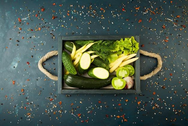 Légumes frais sur boîte en bois sur une pierre foncée. le concept de millesime. concombre de tomates vertes aux asperges vertes de jeunes oignons de maïs sur une surface foncée.