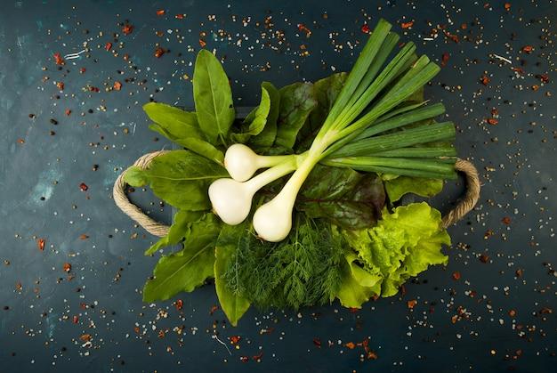 Légumes frais sur boîte en bois sur une pierre foncée. le concept de millesime. oignons verts, feuilles de sorrel, betterave, concombre à l'anoth, sur une surface foncée.