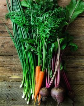 Légumes frais - carottes, betteraves, oignons verts sur bois. récolte.