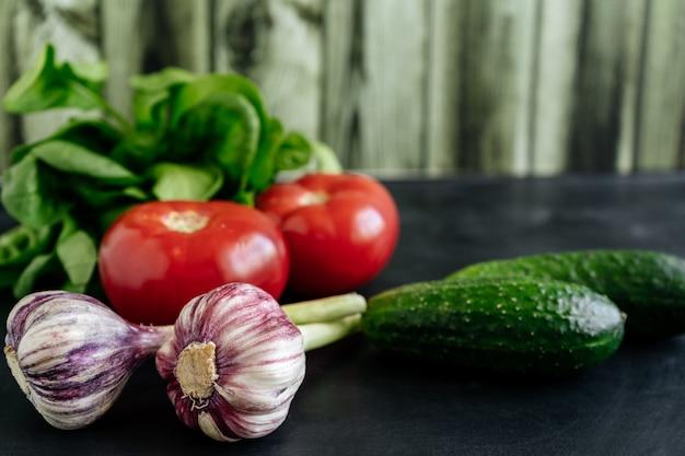 Légumes frais comme les tomates et les concombres près de l'ail