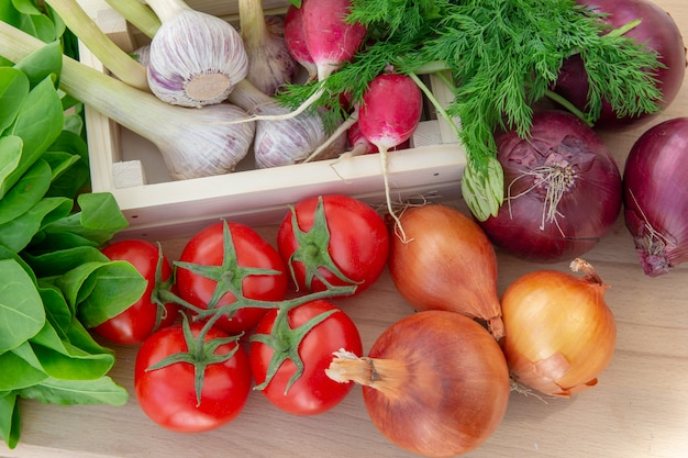 Légumes frais dans une boîte en bois sur fond en bois. le concept d'aliments biologiques sains.