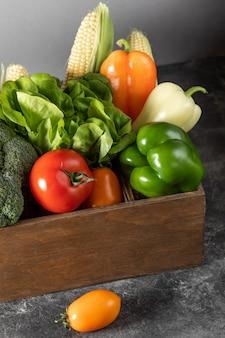 Légumes frais dans une boîte en bois sur un fond en bois foncé