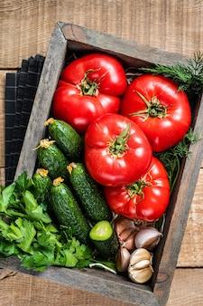 Légumes frais dans une boîte en bois, tomates rouges, concombres verts aux herbes. fond en bois. vue de dessus.