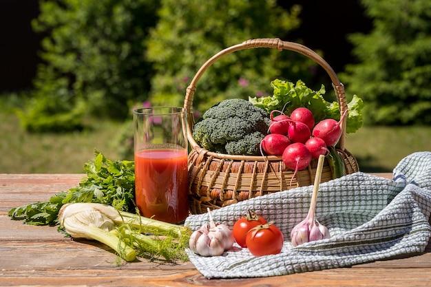 Légumes frais dans un panier et jus de tomate sur la nature verte.