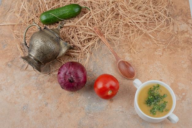 Légumes frais avec une délicieuse soupe sur une surface en marbre