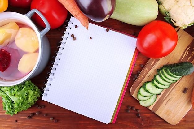Légumes frais et épices et papier pour notes, sur bois