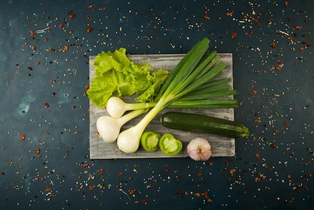 Légumes frais et épices sur une planche en bois sur une pierre foncée. le concept de millesime. les épices du concombre de tomates vertes jus d'asperges de maïs sur une surface foncée.