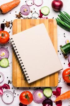 Légumes frais de la ferme autour d'une planche à découper et d'un cahier avec espace copie. tomates, rondelles d'oignon rouge, épices, concombre, carottes. scène de cuisine