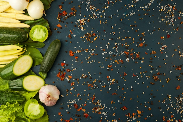 Légumes frais sur un foncé. le concept de millesime. les épices du concombre de tomates vertes jus d'asperges de maïs sur une surface foncée.