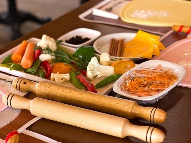 Légumes frais, fromage et rouleau à pâtisserie en bois. atelier de cuisine