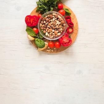 Légumes frais et fruits secs sur une planche à découper contre une table en bois blanche