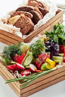 Légumes frais hachés dans une boîte en bois sur une surface blanche