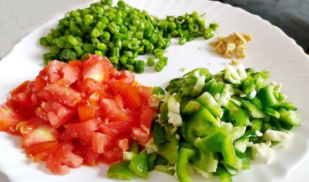 Légumes frais hachés sur une plaque blanche