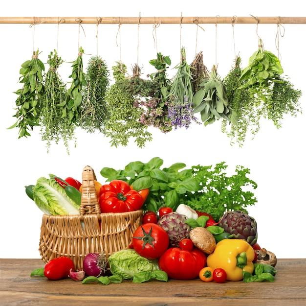 Légumes frais et herbes sur fond en bois. ingrédients alimentaires crus. panier. intérieur de cuisine