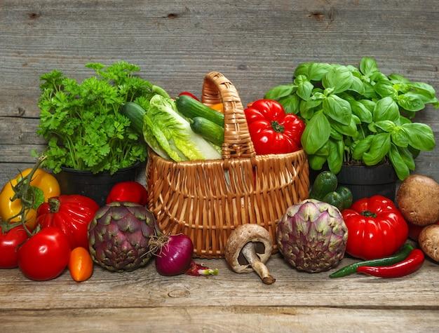 Légumes frais et herbes méditerranéennes sur fond de bois. ingrédients alimentaires crus. concept de bionutrition
