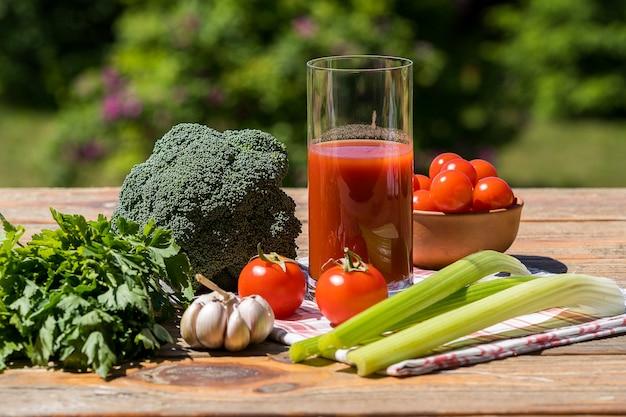 Légumes frais et jus de tomate sur une vieille table en bois, sur fond de nature verdoyante.