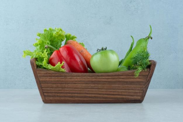 Légumes frais mélangés dans une boîte en bois.