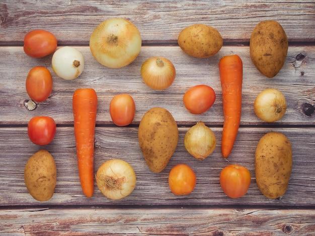 Légumes frais, oignons, tomates, carottes, pommes de terre, placés sur une table en bois, vue de dessus