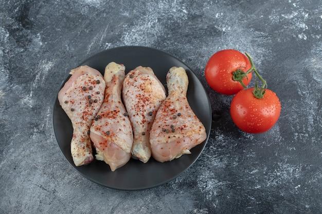 Légumes frais avec pilons de poulet sur fond gris.