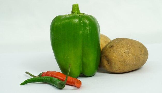 Légumes frais piment capsicum et pomme de terre sur une surface blanche