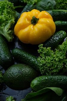 Légumes frais, poivrons jaunes, concombre et salade sur fond noir.