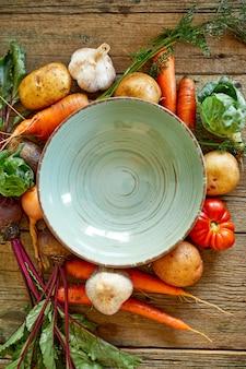 Légumes frais pour la cuisson de la soupe autour d'une assiette vide ronde verte