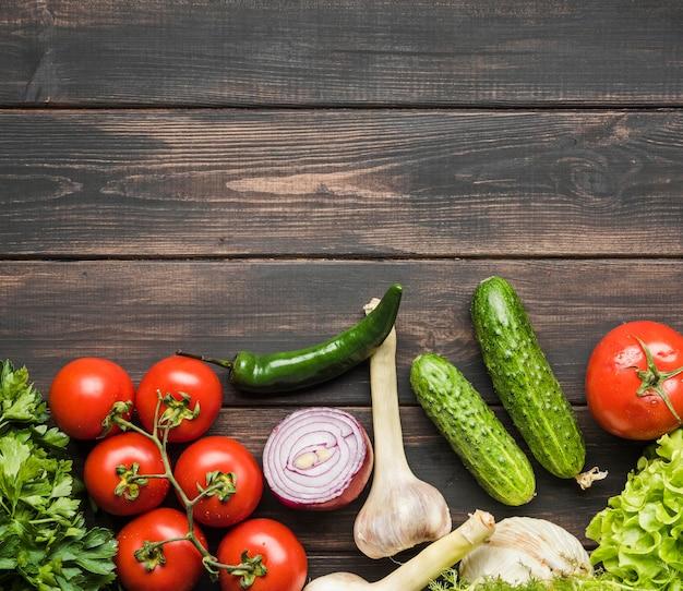 Légumes frais pour salade sur fond de bois