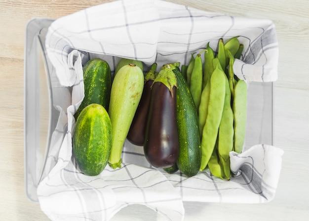 Légumes frais récoltés dans le récipient avec serviette