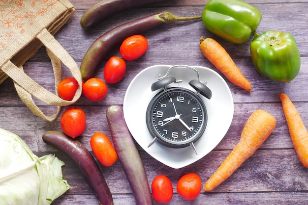 Légumes frais et réveil sur plaque en forme de coeur sur table